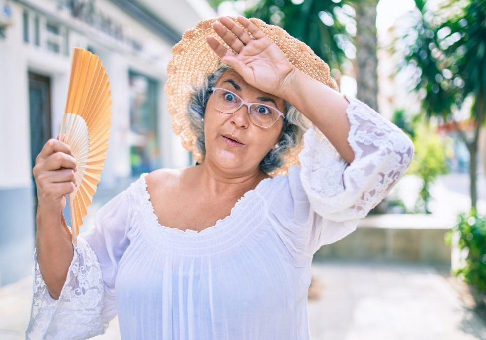 senior woman wiping sweat off her brow during heatwave